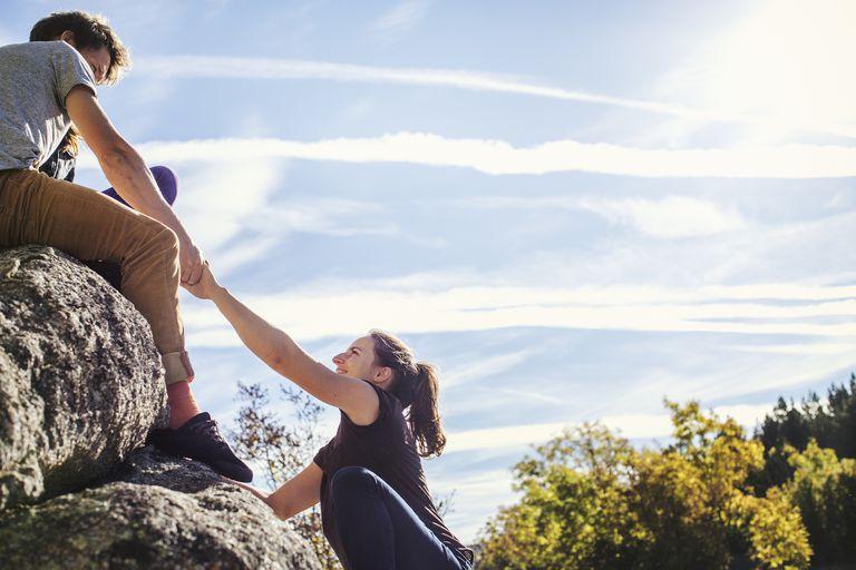 Man helping female friend climb rock