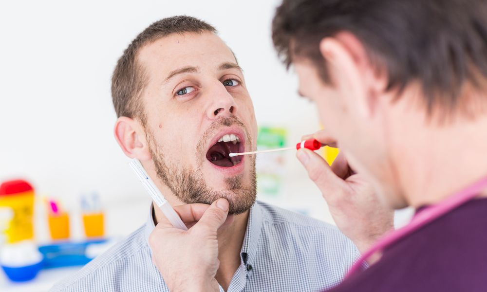 Collecting a throat culture.