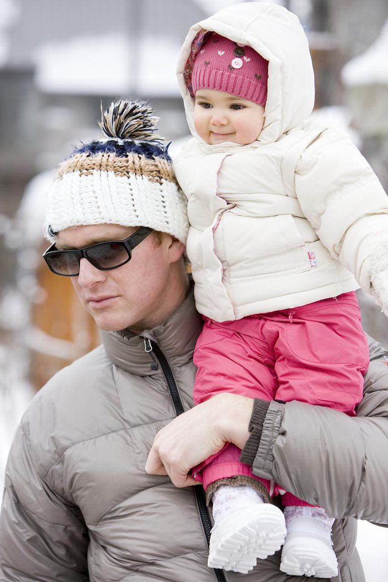 Father carrying baby girl (6-11 months) on shoulders, outdoors