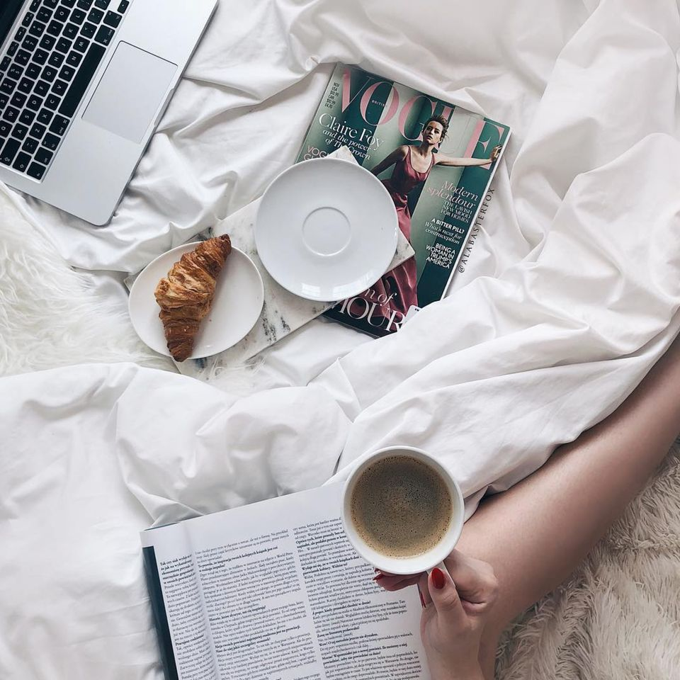 Bed with Vogue magazine and coffee