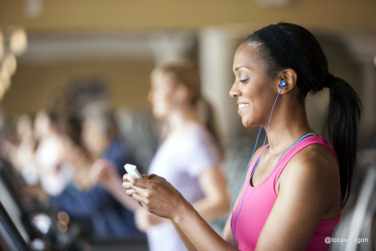 Woman using a mobile phone on a treadmill in a gym