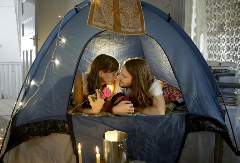 Young couple lying in tent rubbing noses
