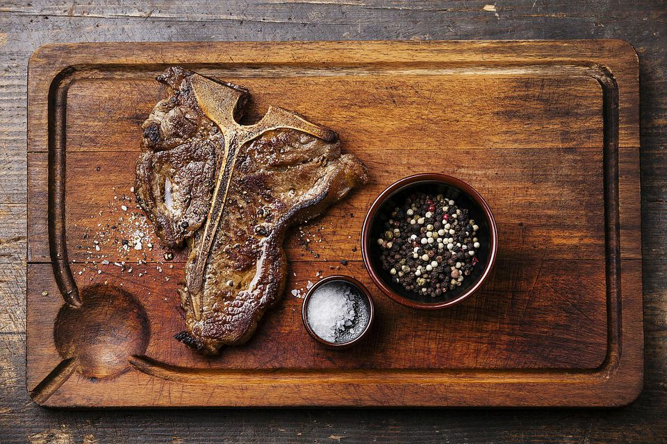 Grilled T-Bone Steak with salt and pepper on cutting board on dark wooden background