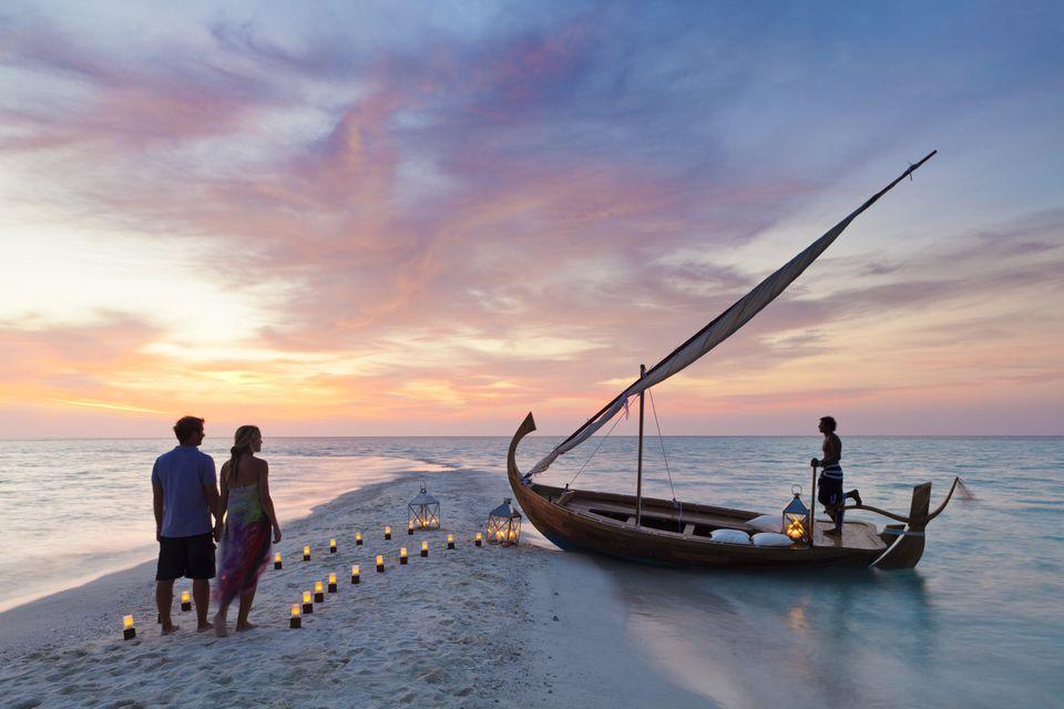 Maldives, Rasdhoo Atoll, Kuramathi Island. A couple wait to board a traditional Dhoni on the sandbank at Kuramathi Island Resort. MR.