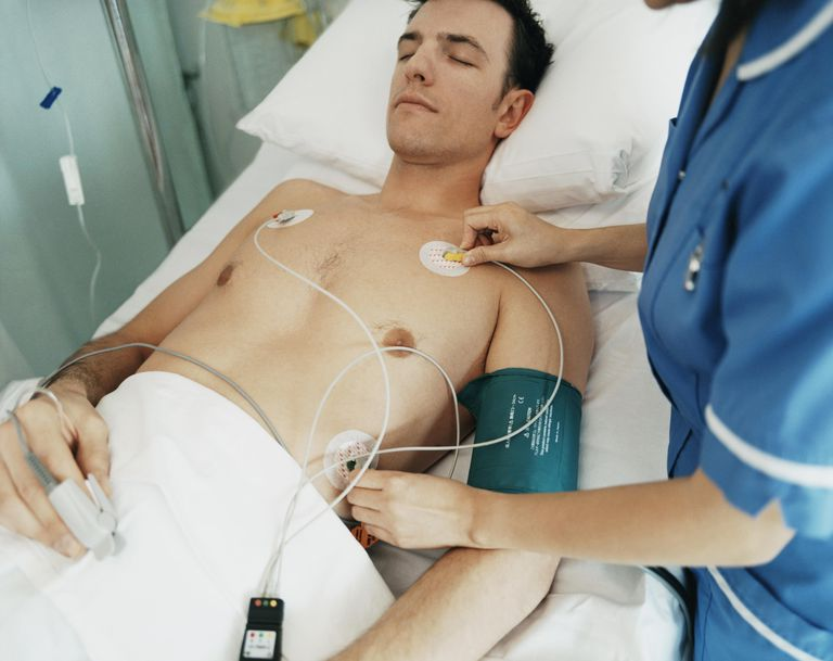 Nurse Adjusts the ECG Pads on a Male Hospital Patient's Chest