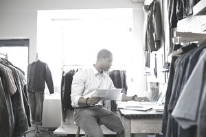 Business owner working at laptop in clothing shop