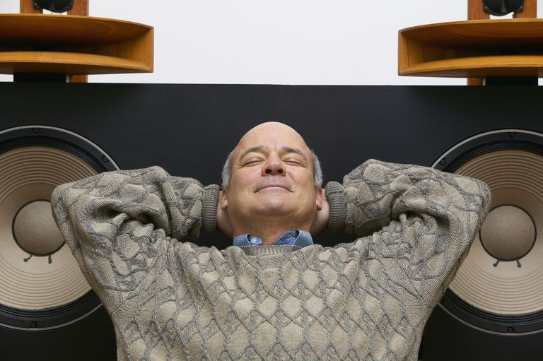 A content man with eyes closed, leaning backwards against large stereo speakers