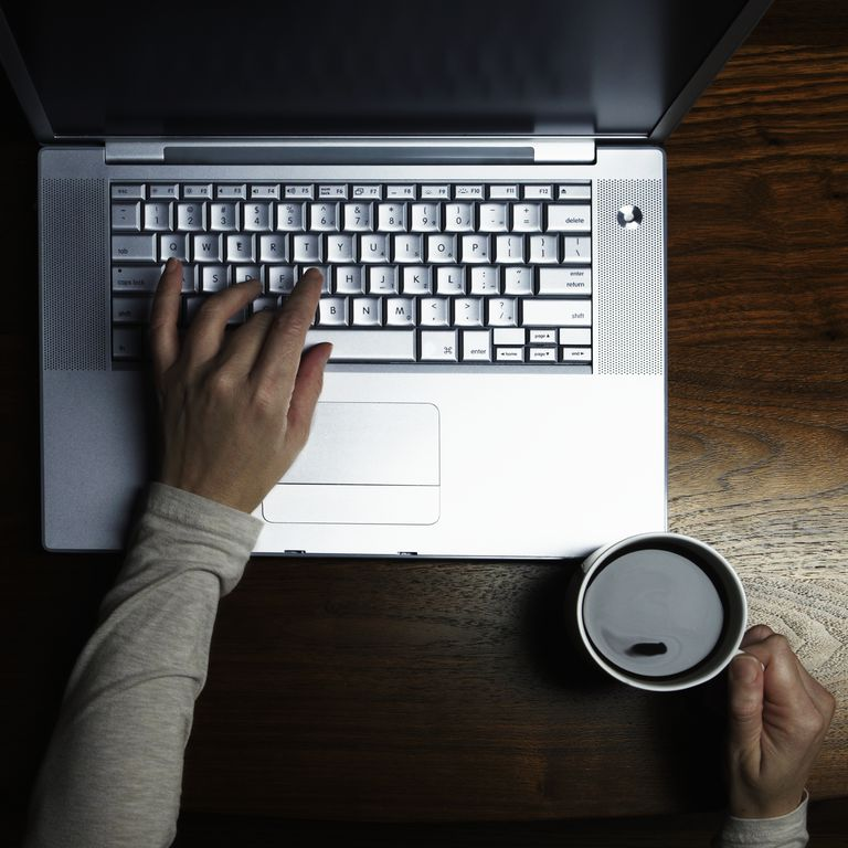 Woman drinks coffee while typing on computer