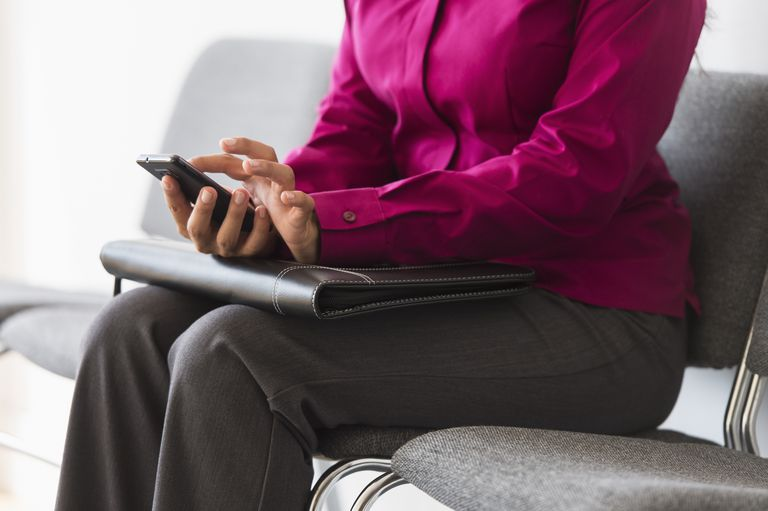 woman using cell phone while waiting for job interview