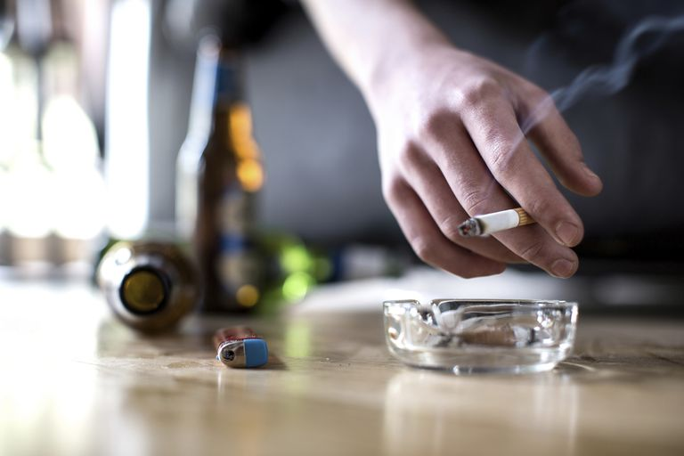 man holding a cigarette with beer bottles on the floor