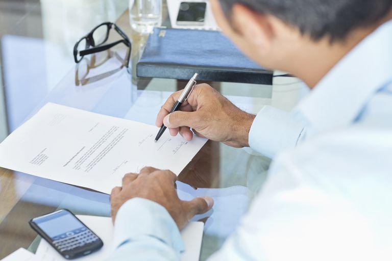Businessman making notes at desk