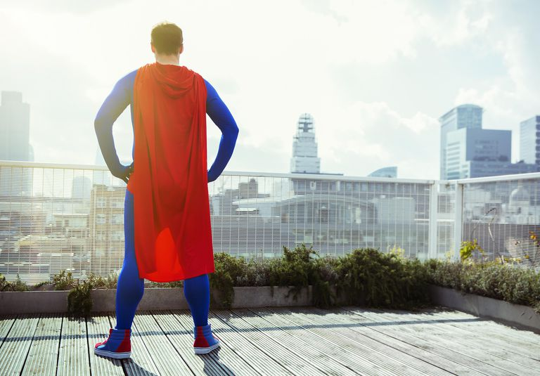 Super hero on a deck looking at city skyline.