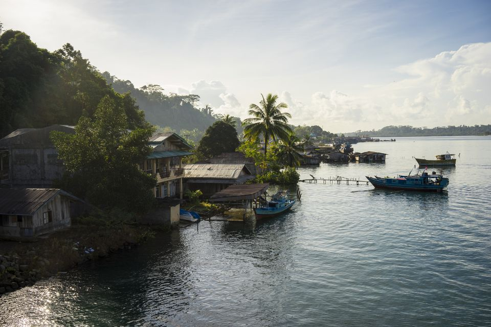 Fishing boats and ramshackle houses on coastline.