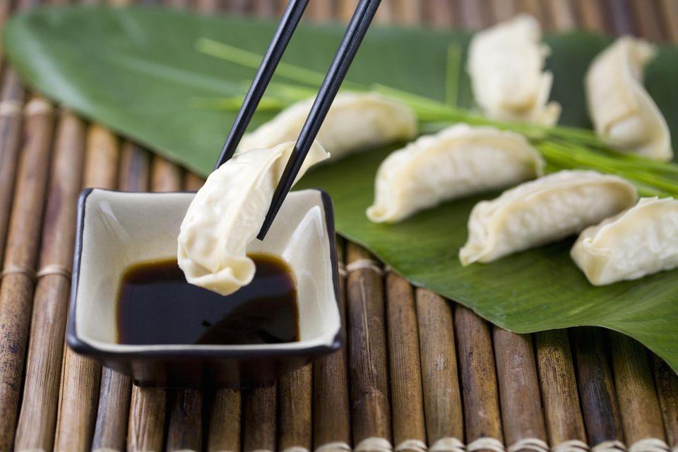 Chopsticks with Gyoza dumplings and soy sauce