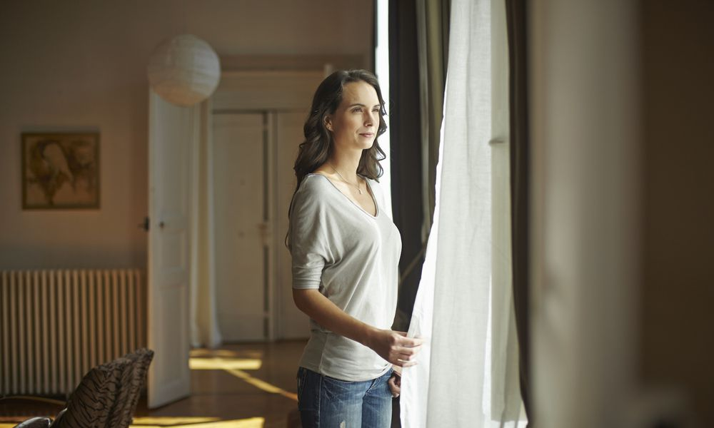 Young woman looking out of apartment window