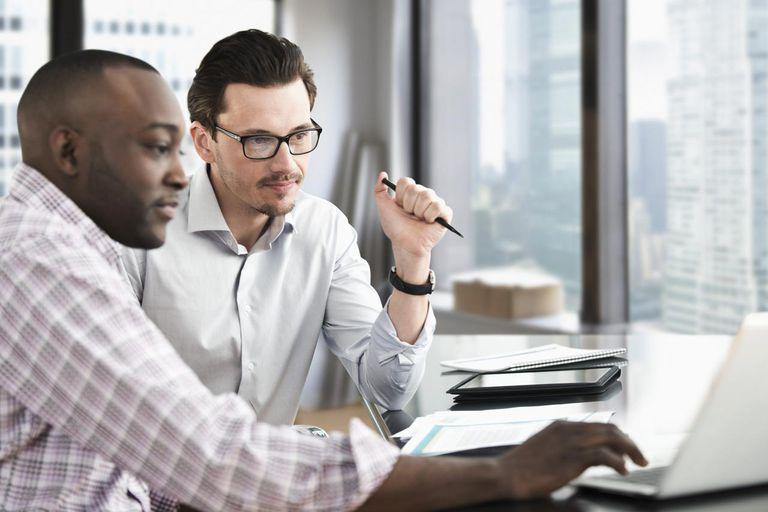 Business men looking at laptop