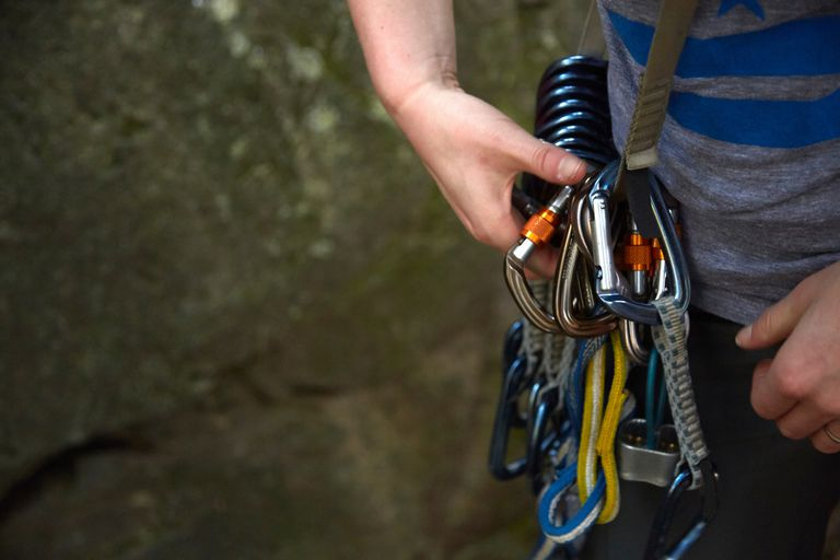 Rock climber preparing safety harness
