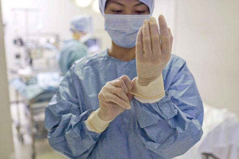 Female surgeon adjusting medical glove in hospital