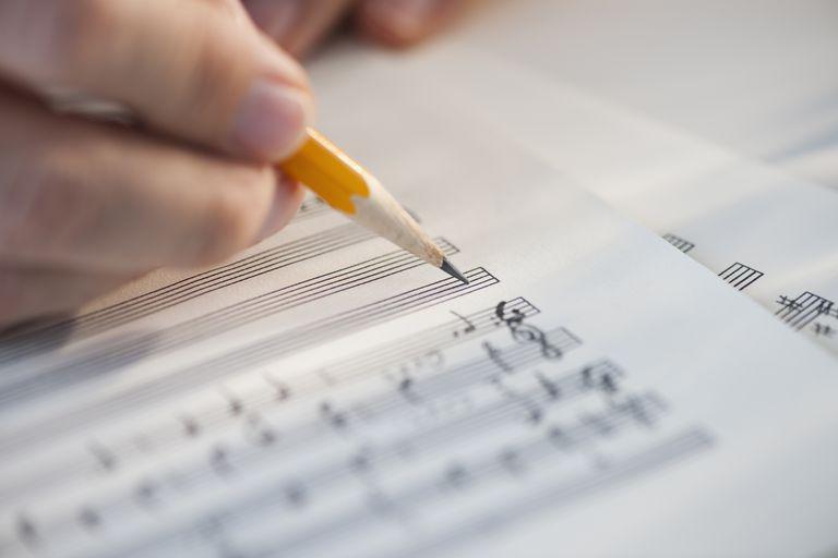 man writing sheet music