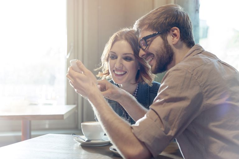 Couple looking at phone in cafe