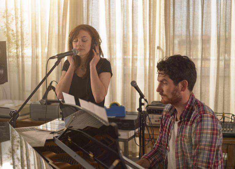 Man at piano. Woman in headphones singing