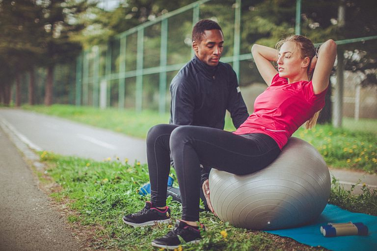 Woman strength training with trainer in park