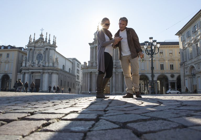 Two travelers standing in a piazza in Italy
