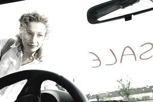Woman looking at car for 'Sale', view through windshield