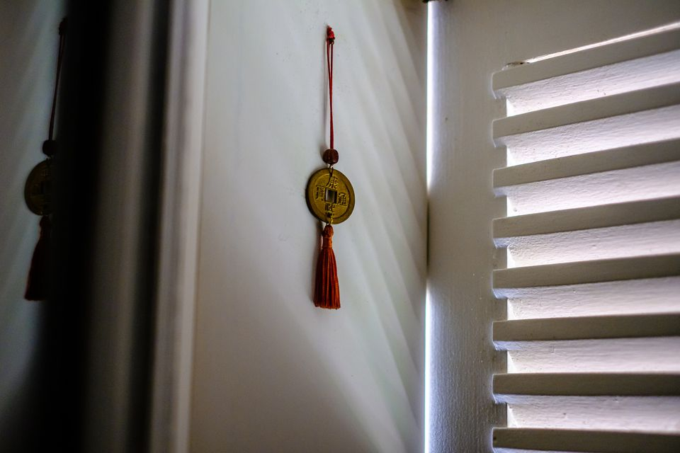 A feng shui charm hung up by a window
