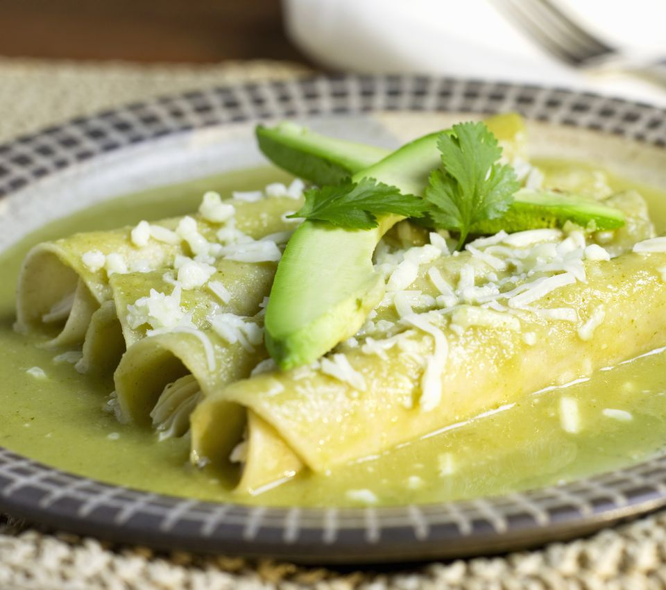 Three chicken enchiladas with tomatillo sauce, cheese and avocado