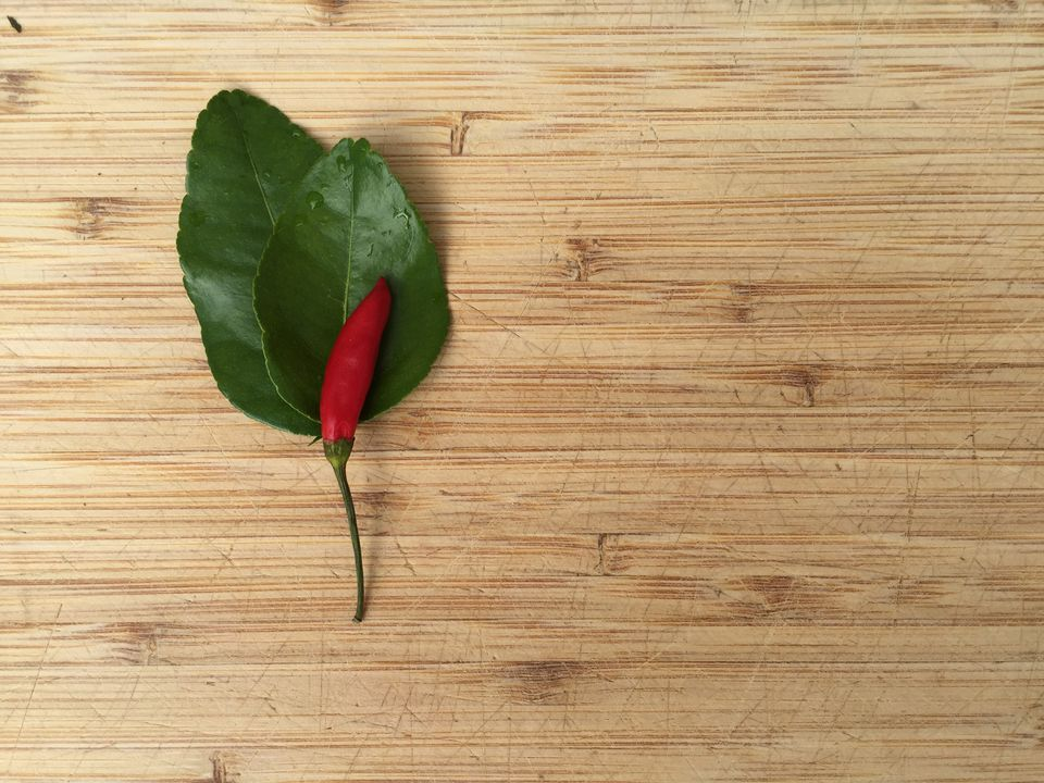 Flat lay. Overhead high angle POV of kaffir lime leaves and a red chili pepper on a bamboo chopping block background.