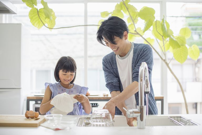 father and daughter washing dishes