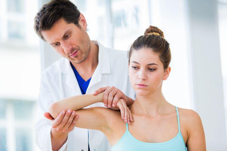 Doctor examining woman's elbow.