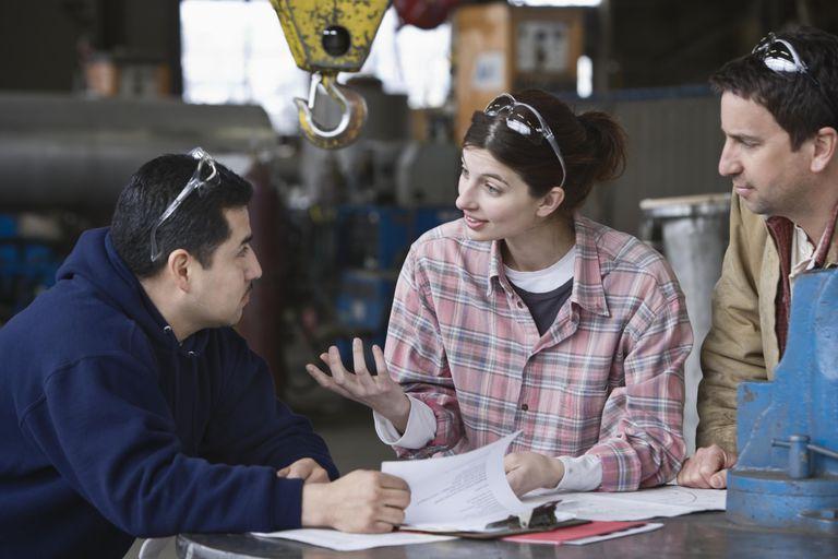Three factory workers in informal meeting