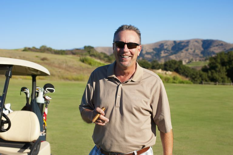 Man with cigar playing golf at an early retirement age.