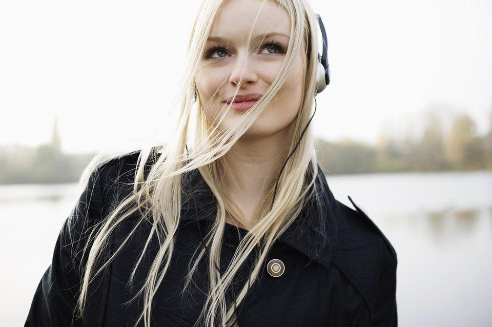 Woman listening to headphones in park