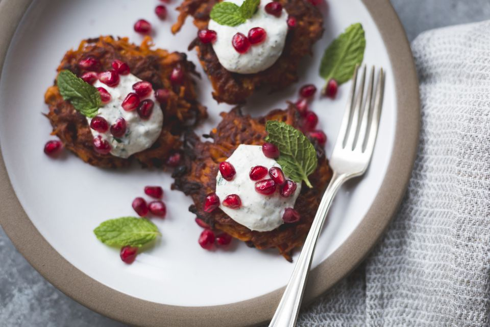 Harissa sweet potato latkes with spiced yogurt, mint and pomegranate, gluten-free.