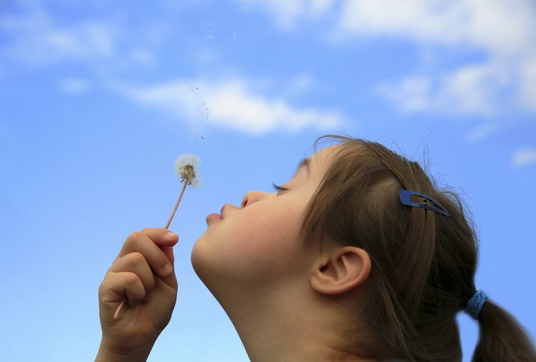 girl with Down syndrome blowing on a dandelion
