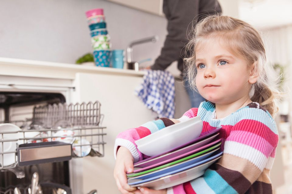 Girl holding stack of plates