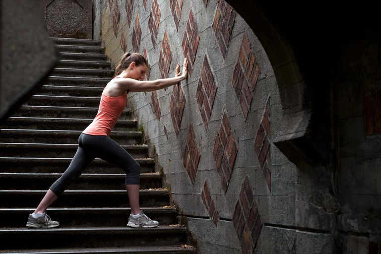 Woman stretching on city steps