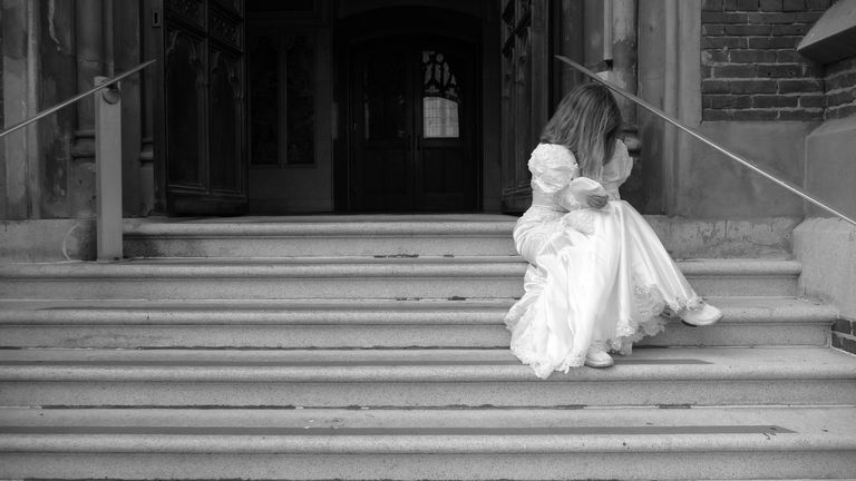Bride sitting on church steps with her head down.
