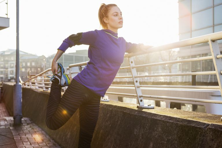 female runner stretching leg in urban space