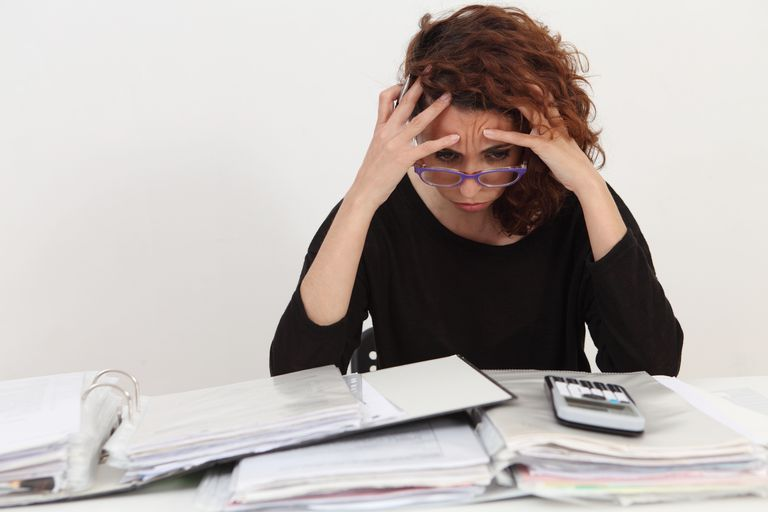 woman looking overwhelmed with calculator and binders in front of her