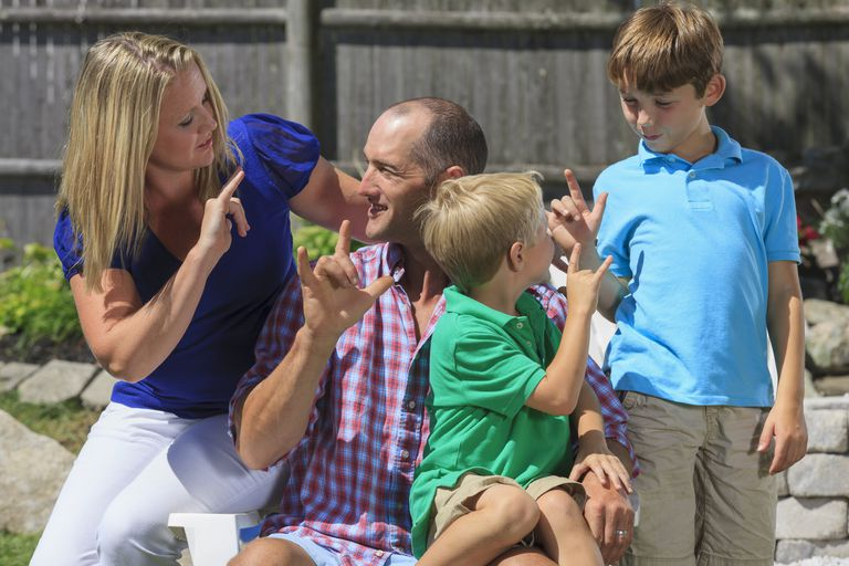 Happy family with hearing impairments signing I love you in American sign language