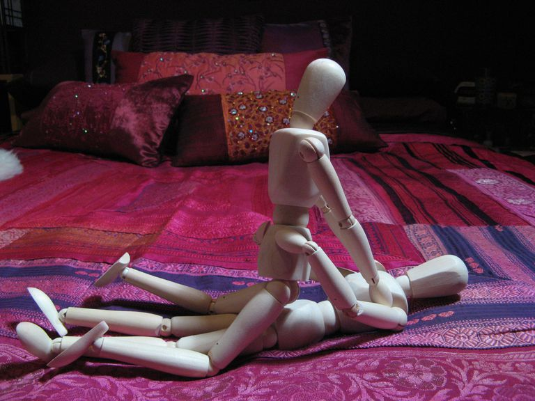 Wooden dolls illustrating the woman on top sex position