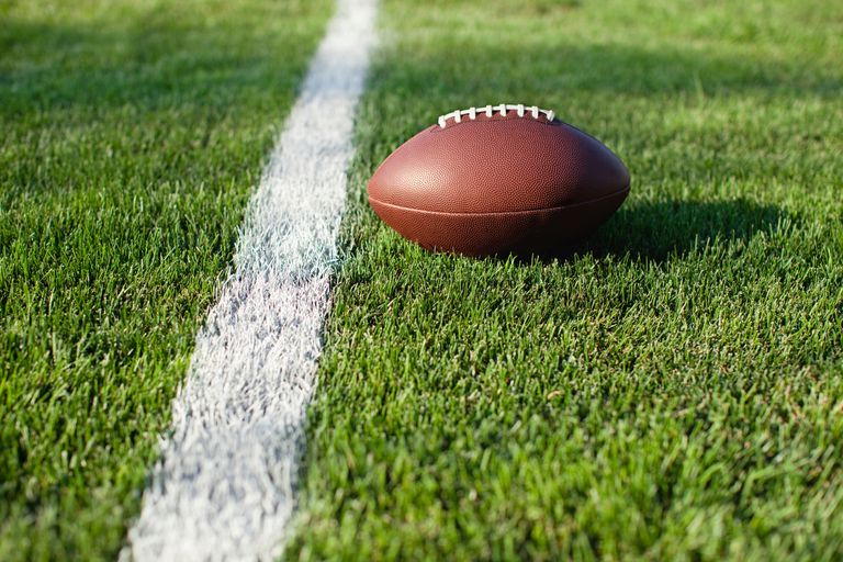 American Football Ball Close To White Line On Playing Field