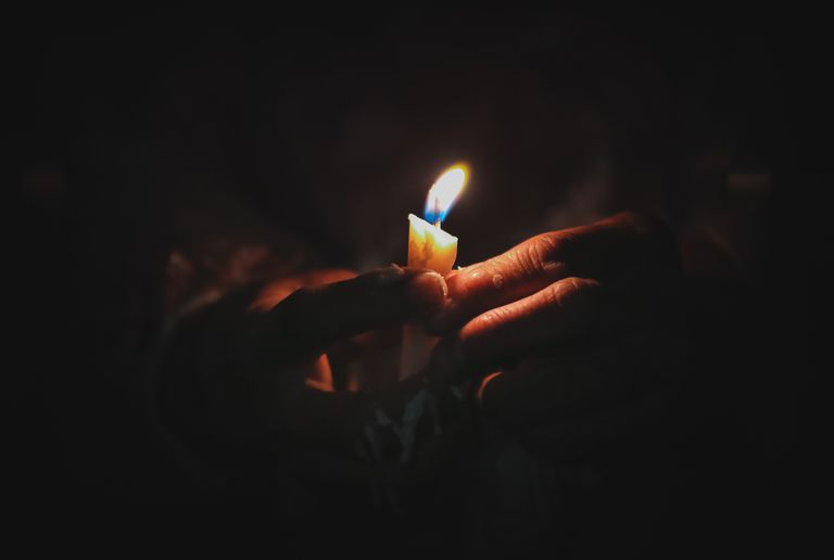 Cropped Image Of Hand Holding Illuminated Candle In Darkroom