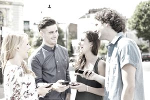 Group of friends laughing with smart phones.