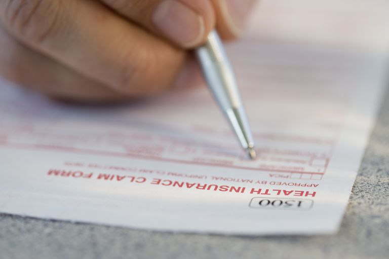 man filling out health insurance claim form