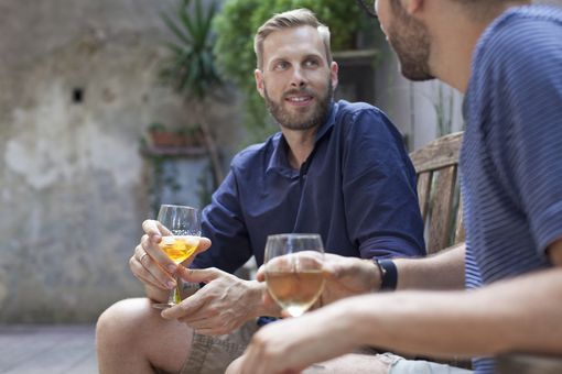 two men enjoying drinks together and talking
